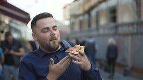 Szczęśliwy mężczyzna je kawałek pizza z uśmiechem na twarzy wśród ulicy zbiory