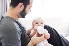 Szczęśliwy mężczyzna karmienia mleko dziewczynka w domu Zdjęcia Stock