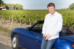 Szczęśliwy mężczyzna kierowca jedzie błękitnego odwracalnego samochodowego Młodego męskiego dorosłego nowego właściciela luksusu  obraz royalty free