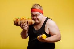 Szczęśliwy mężczyzna narządzanie jeść hamburger i spojrzenie przy kamerą obrazy stock