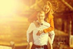 Szczęśliwy mężczyzna niesie jego dziewczyny na plecy dalej na moscie o fotografia stock