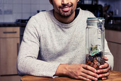 Szczęśliwy mężczyzna obsiadanie w kuchni z prosiątko bankiem Zdjęcia Royalty Free