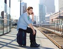 Szczęśliwy mężczyzna opowiada na telefonu komórkowego czekaniu dla pociągu Fotografia Stock
