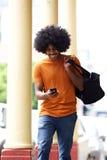 Szczęśliwy mężczyzna patrzeje telefon komórkowego w mieście z torbą Zdjęcie Royalty Free