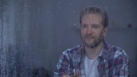 Szczęśliwy mężczyzna pije brandy samotnie na deszczowym dniu, świętuje kariery promocję zbiory