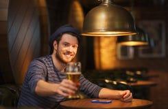 Szczęśliwy mężczyzna pije piwo przy barem lub pubem fotografia royalty free
