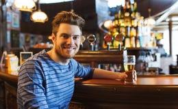 Szczęśliwy mężczyzna pije piwo przy barem lub pubem Zdjęcie Stock