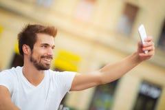 Szczęśliwy mężczyzna robi selfie fotografii na ulicie Zdjęcie Royalty Free