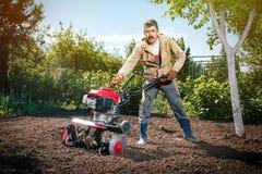 Szczęśliwy mężczyzna rolnik orze ziemię z kultywatorem, przygotowywa je Zdjęcie Stock
