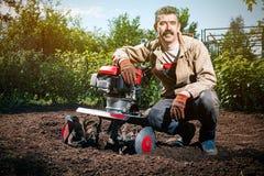 Szczęśliwy mężczyzna rolnik orze ziemię z kultywatorem, przygotowywa je Obraz Stock