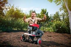 Szczęśliwy mężczyzna rolnik orze ziemię z kultywatorem, przygotowywa je Fotografia Royalty Free