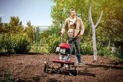 Szczęśliwy mężczyzna rolnik orze ziemię z kultywatorem, przygotowywa je Fotografia Stock