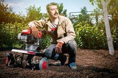 Szczęśliwy mężczyzna rolnik orze ziemię z kultywatorem, przygotowywa je Zdjęcia Royalty Free