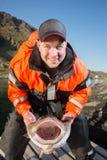 Szczęśliwy mężczyzna rybak trzyma rybich blaszek ogromnego dorsza pionowy Zdjęcia Royalty Free