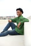 Szczęśliwy mężczyzna siedzi outdoors z jabłkiem Zdjęcia Royalty Free