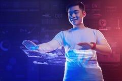 Szczęśliwy mężczyzna stawia jego wręcza out podczas gdy kontrolujący hologram Obraz Royalty Free