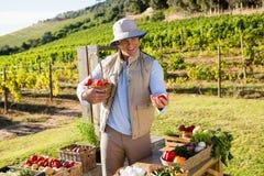 Szczęśliwy mężczyzna trzyma świeżych warzywa przy kramem Obrazy Royalty Free