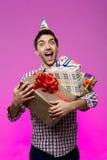 Szczęśliwy mężczyzna trzyma urodzinowych prezenty w pudełkach nad purpurowym tłem Obrazy Royalty Free