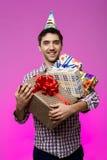 Szczęśliwy mężczyzna trzyma urodzinowych prezenty w pudełkach nad purpurowym tłem Zdjęcia Royalty Free