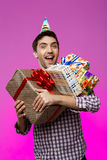 Szczęśliwy mężczyzna trzyma urodzinowych prezenty w pudełkach nad purpurowym tłem Zdjęcia Stock