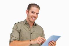 Szczęśliwy mężczyzna używa pastylka komputer osobistego Obrazy Stock