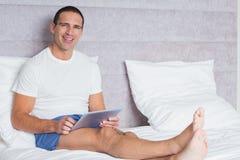 Szczęśliwy mężczyzna używa pastylka komputer osobistego na łóżku Fotografia Royalty Free