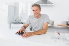 Szczęśliwy mężczyzna używa pastylka komputer osobistego w kuchni Obrazy Stock