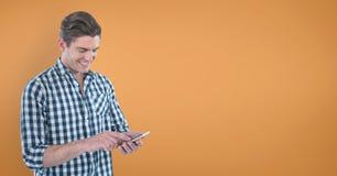 Szczęśliwy mężczyzna używa telefon przeciw pomarańczowemu tłu Zdjęcie Stock