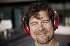 Szczęśliwy mężczyzna w czerwonych hełmofonach Obrazy Royalty Free