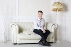 Szczęśliwy mężczyzna w koszula i spodniach siedzi na białej skóry kanapie Obraz Royalty Free