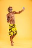 Szczęśliwy mężczyzna w swimwear robi selfie fotografii na smartphone Zdjęcie Royalty Free