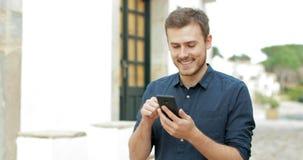 Szczęśliwy mężczyzna wyszukuje telefon komórkowy zawartość w ulicie zbiory