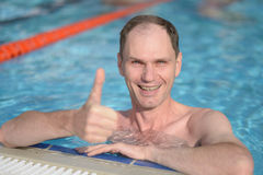 Szczęśliwy mężczyzna z aprobatami w pływackim basenie Zdjęcie Stock