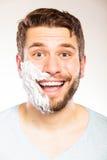 Szczęśliwy mężczyzna z golenie śmietanki pianą na połówce twarz zdjęcia royalty free