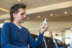 Szczęśliwy mężczyzna z małym wzorcowym samolotem wśrodku lotniska Zdjęcie Royalty Free