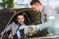 Szczęśliwy mężczyzna z samochodowym handlowem w auto przedstawieniu lub salonie Obraz Royalty Free