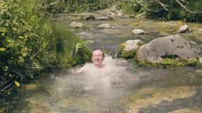 Szczęśliwy mężczyzna zamaczał i pluśnięcie woda od halnej wiosny Mężczyzna kąpanie w rzece zdjęcie wideo