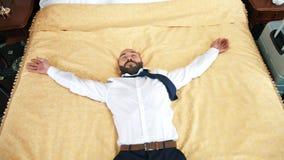 Szczęśliwy męski biznesmena doskakiwanie na łóżku przy pokojem hotelowym ma podróży służbowej zwolnione tempo zbiory