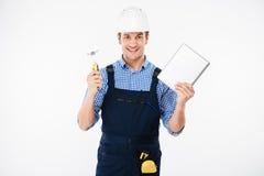 Szczęśliwy męski budowniczy pokazuje kciuk up i trzyma komputer osobisty pastylkę Obrazy Stock