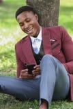 Szczęśliwy męski czarny pracownik patrzeje jego telefon obraz royalty free