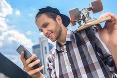 Szczęśliwy męski deskorolkarz używa telefon komórkowego Zdjęcia Stock
