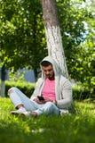 Szczęśliwy męski dorosły używa jego smartphone w parku Zdjęcie Royalty Free