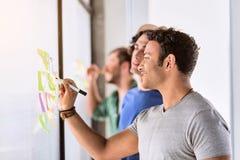 Szczęśliwy męski freelancer robi notatkom na majcherze Zdjęcia Royalty Free