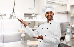 Szczęśliwy męski indyjski szef kuchni przedstawia restauracyjną kuchnię zdjęcia royalty free