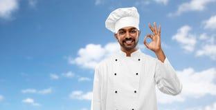 Szczęśliwy męski indyjski szef kuchni w toque pokazuje ok gest zdjęcie stock