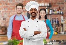Szczęśliwy męski indyjski szef kuchni w toque przy kulinarną klasą zdjęcia stock
