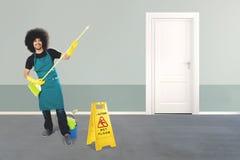 Szczęśliwy męski janitor bawić się miotłę w hotelu Obraz Stock