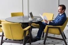 Szczęśliwy męski kierownik pracuje z papierami w wygodnym biurze Zdjęcie Royalty Free