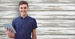 Szczęśliwy męski modniś trzyma cyfrową pastylkę przeciw drewnianej ścianie Fotografia Stock