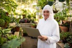 Szczęśliwy męski naukowiec używa laptop przy szklarnią Fotografia Stock